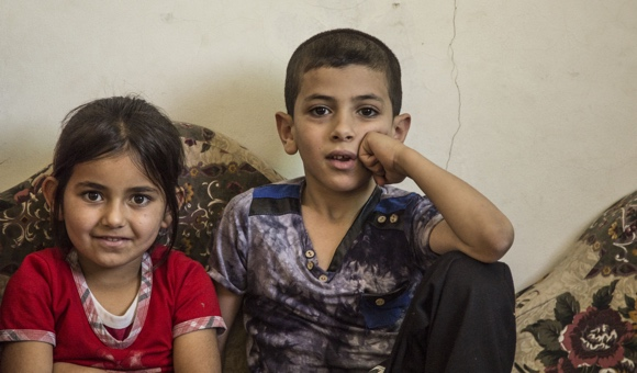 Mohammad Musa Eid's niece, 5, and son, 7, sit together inside the second-floor apartment in June, 2016,  after Israel had issued the demolition order. (Photo: DCIP / Cody O'Rourke)