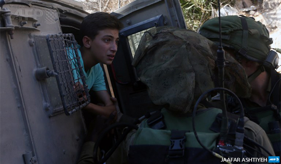 Israeli soldiers remove a Palestinian youth from a military vehicle in the West Bank village of Burin on September 15, 2016, following scuffles with Israeli settlers. (Photo: AFP / Jaafar Ashtiyeh)
