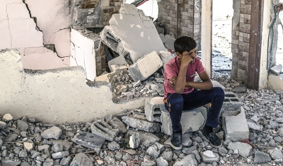 Boys sits on cinder block after Israel's punitive demolition of Mohammad Makhamra family home