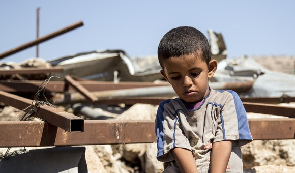 Daifallah's youngest son, sits on broken concrete blocks and twisted, steel where his home once was in Aqaba, Tubas governorate. (Photo: DCIP / Cody O'Rourke)