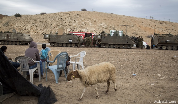 Israeli army vehicles park next to a Palestinian family compound during an Israeli military training in the northern Jordan valley, West Bank, on December 8, 2016. (Photo: ActiveStills / Keren Manor)