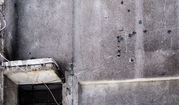 Bullet holes can be seen on the external wall on the second floor of an apartment building in Balata refugee camp. (Photo: DCIP / Cody O'Rourke)