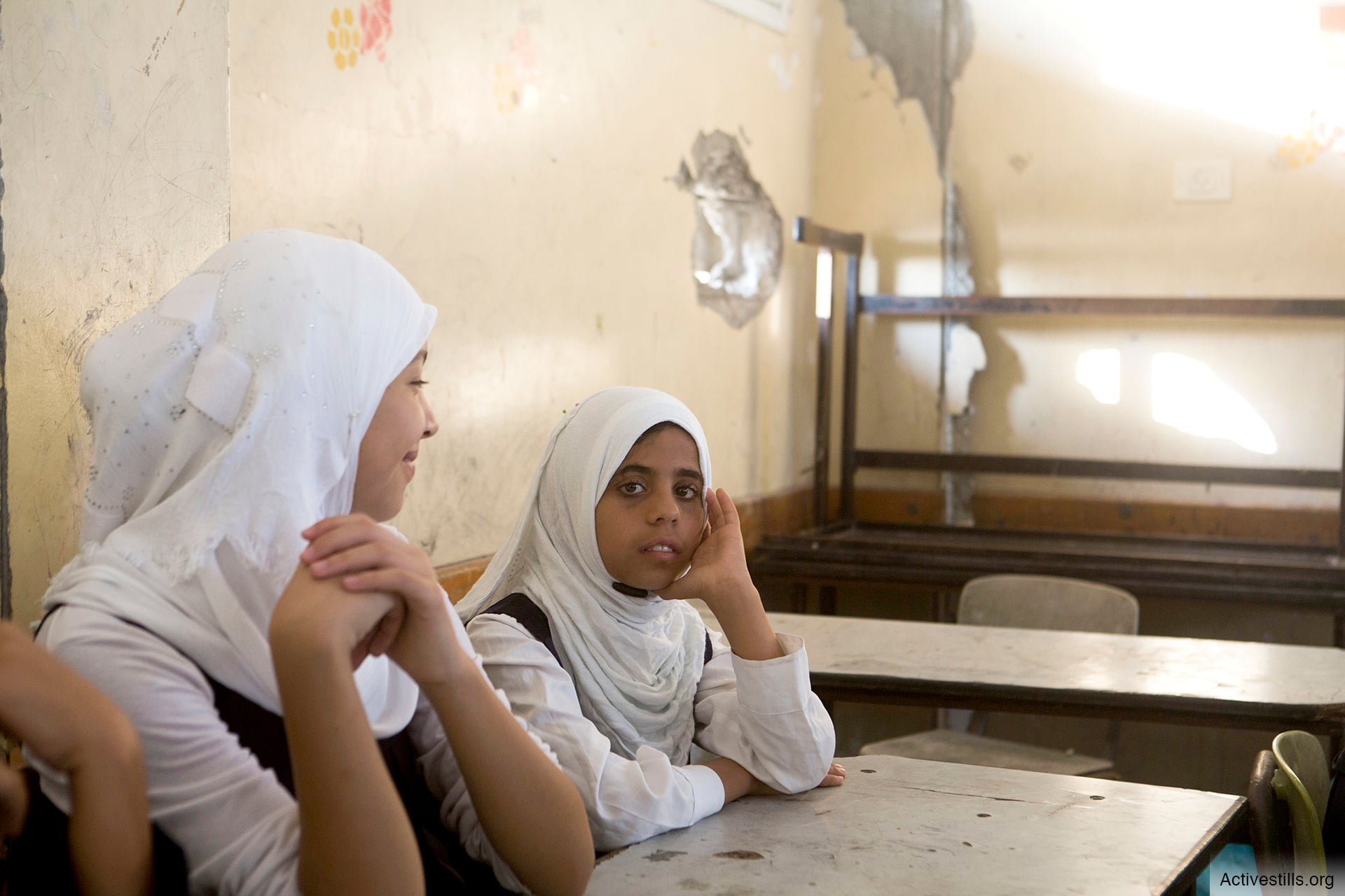 Students in the Shuja'iyya neighborhood of Gaza City attend class in a school damaged during Israel's 2014 military assault. (Photo: ActiveStills / Anne Paq)