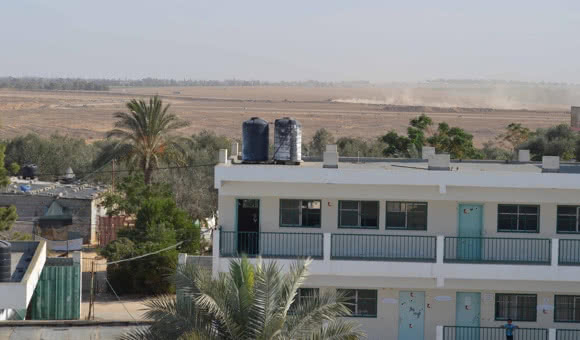 Israeli military vehicles travel along the Israel-Gaza border, approximately 300 meters (33 yards) from Khuza'a Secondary Boys school in Khan Younis, southern Gaza. (Source: courtesy of the Ministry of Education).