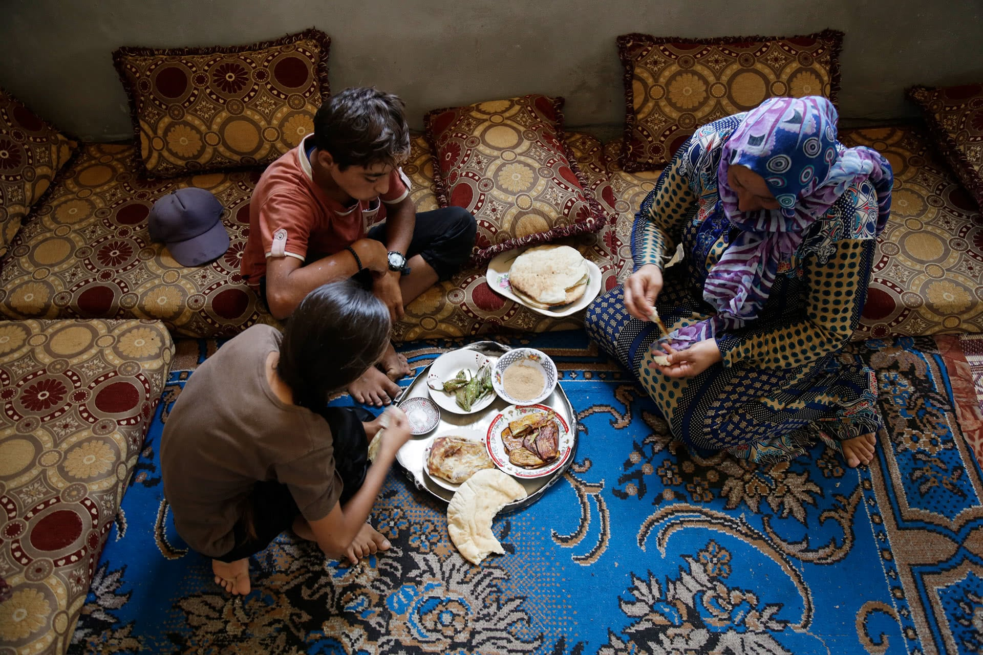 Ahmad Abu Samra, 13, sits on the floor for a meal of bread, eggplant and peppers with his mother and sister. (Photo: DCIP / Saud Abu Ramadan)