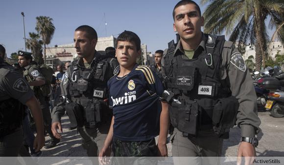 Israeli border policemen arrest a Palestinian child in East Jerusalem in May 2013.
