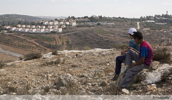Palestinian boys sit on a hill overlooking the Israeli settlement of Halamish in the occupied West Bank.