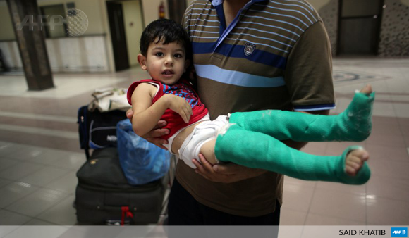 A Palestinian father carries his wounded son as they wait for permission to cross into Egypt at the Rafah border on August 28.
