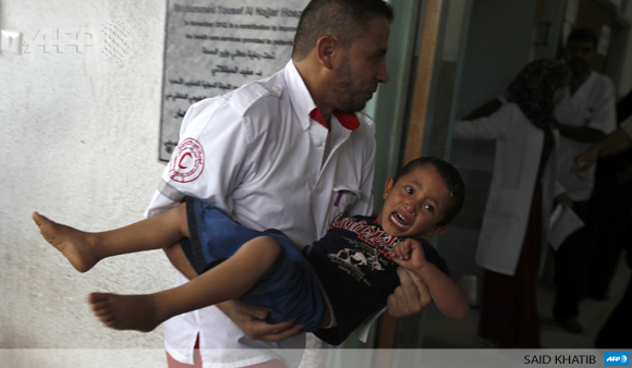 A member of the Palestinian Red Crescent Society carries an injured child in Rafah on July 17.