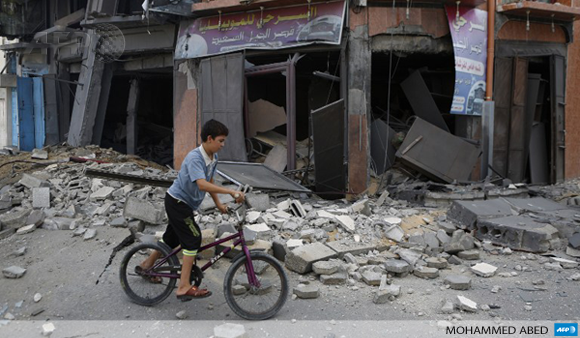 A Palestinian boy rides his bicycle past a damaged building following an Israeli air strike on July 17 in Gaza City.