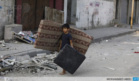 A Palestinian boy carries a mattress he recovered from his family's damaged apartment in Gaza City on July 22.