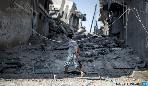 A Palestinian boy walks amid the rubble of destroyed buildings on July 27 in the Shuja'iyya district of Gaza City.