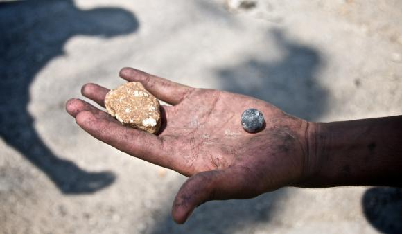 A child holds a rubber-coated metal bullet. (DCIP / Dylan Collins)