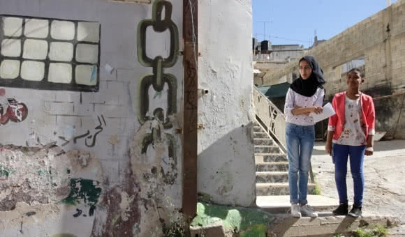 Two Palestinian girls stand on the steps of the Not To Forget Society's building in Jenin refugee camp, West Bank