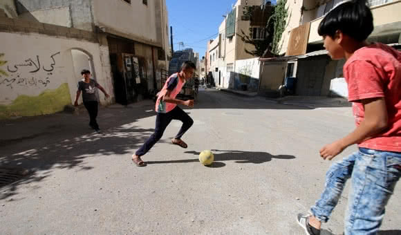 Palestinian children play soccer in the streets of Jenin refugee camp in the northern West Bank