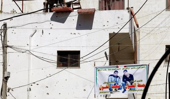 Damage from bullets and fragments cover the walls of a Palestinian house in Jenin refugee camp, West Bank