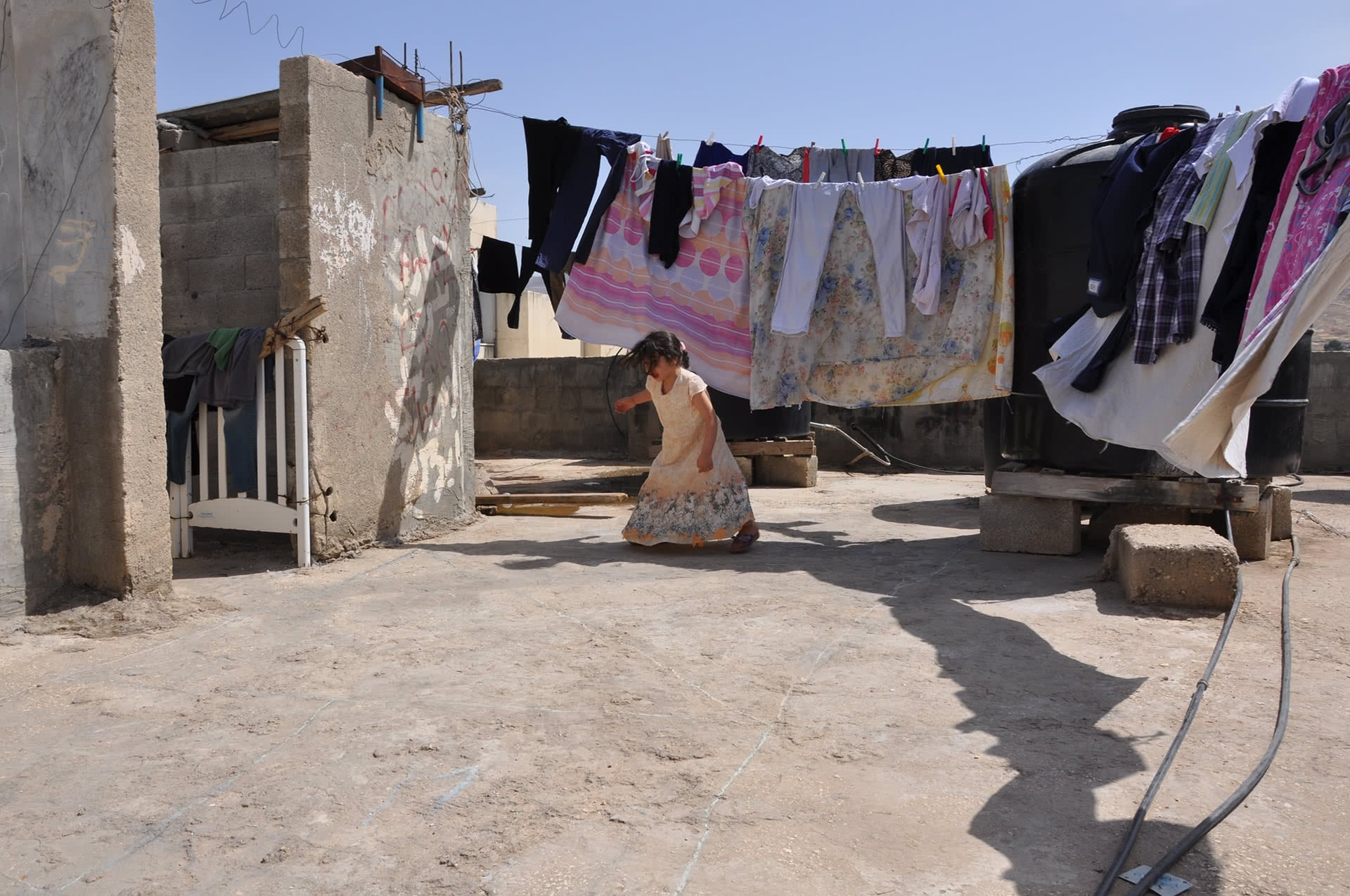 Tasneem Abd al-Jawad, 4, plays a chalk game on the roof of her home in Fara'a refugee camp. (Photo: DCIP / Emily Thomas)