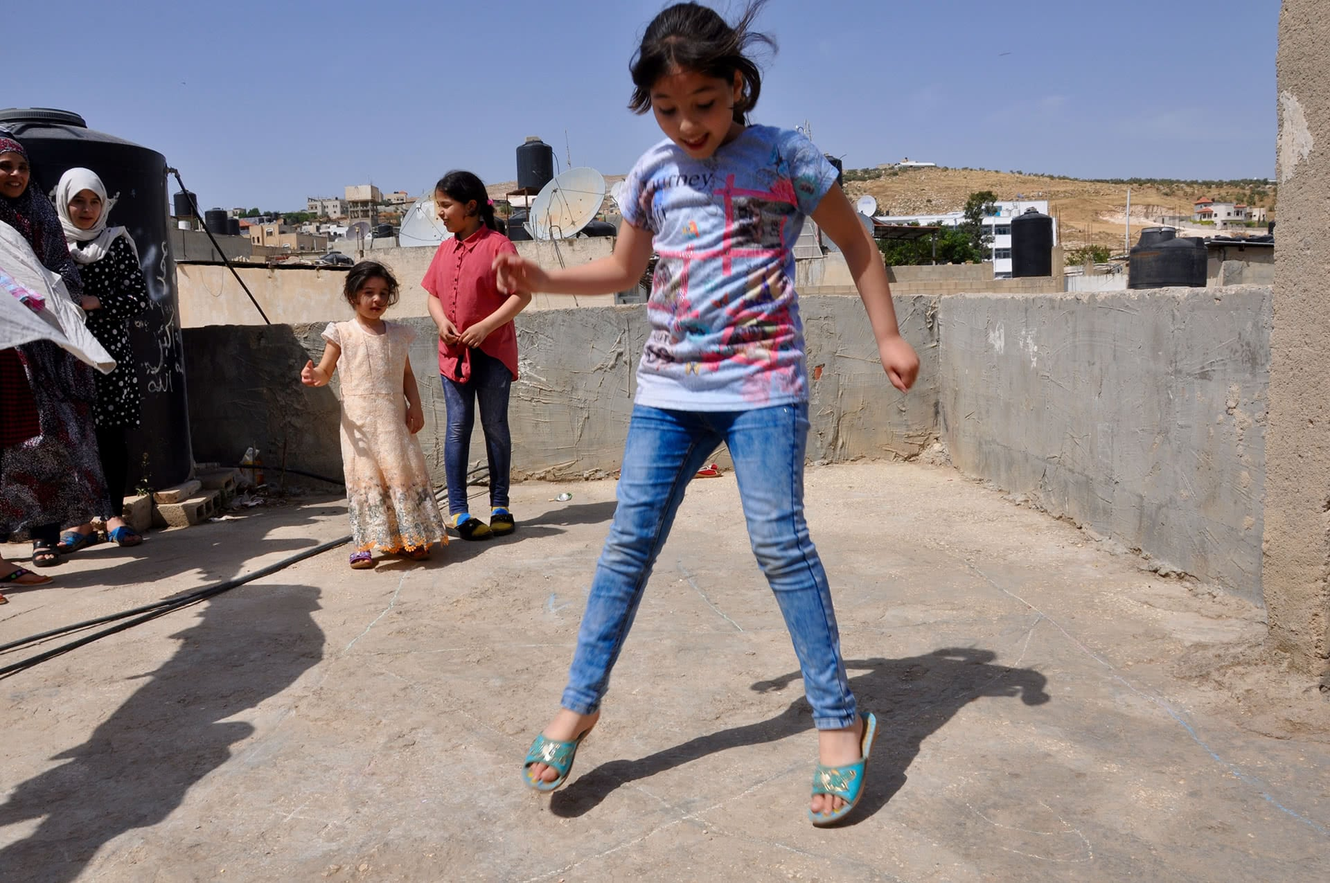 Hanan Abd al-Jawad, 9, plays on the roof with her sisters in Fara'a refugee camp. (Photo: DCIP / Emily Thomas)