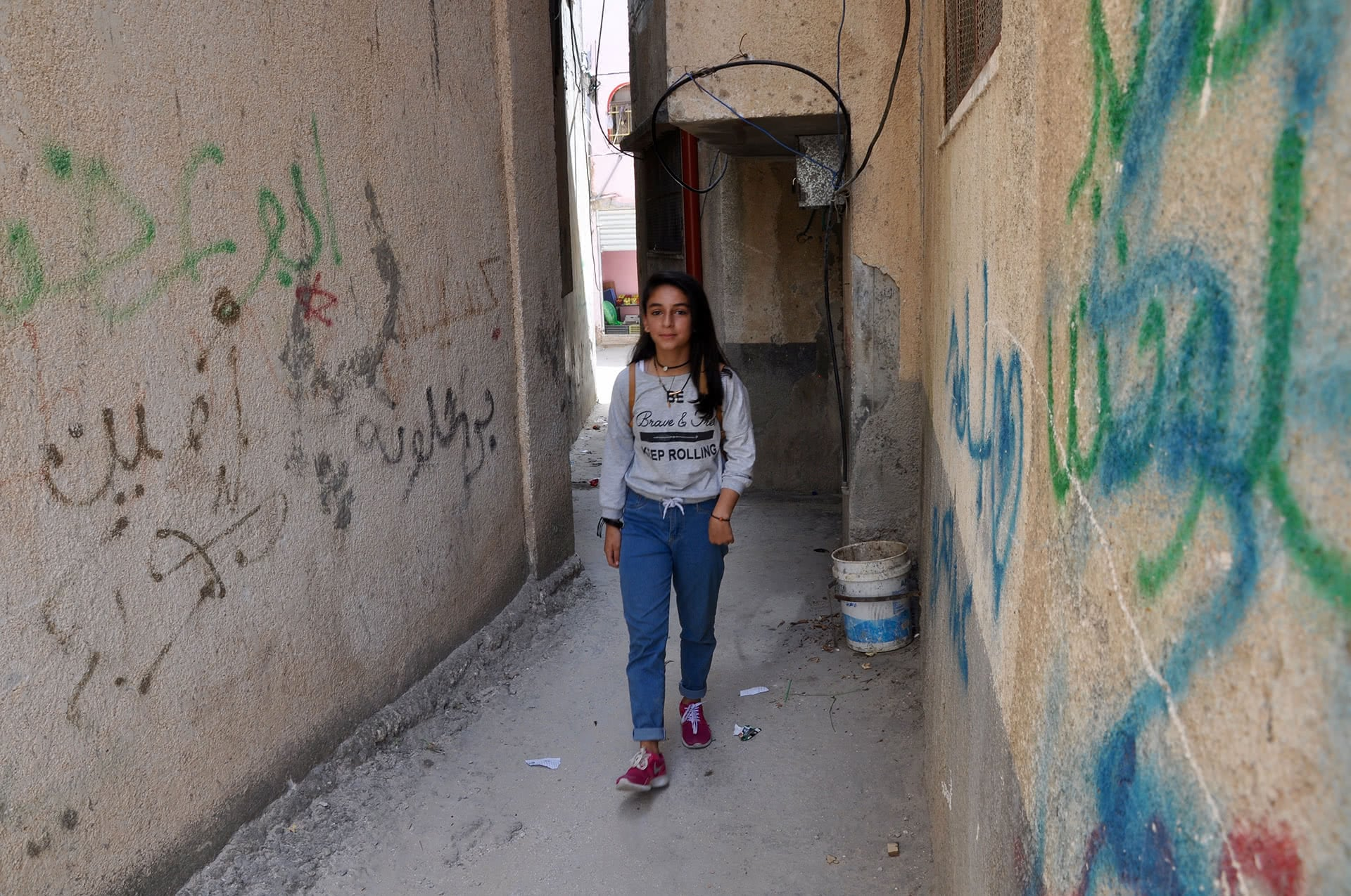 Sara Einajeh, 14, walks through streets she said are unsafe for playing. (Photo: DCIP / Emily Thomas. )