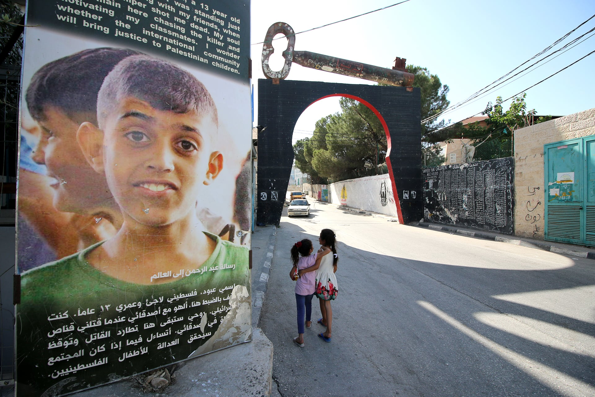 Palestinian children walk in Aida refugee camp by a poster of resident Abdel-Rahman Obeidallah, who was killed by the Israeli army at the age of 13. (Photo: DCIP/ Ahmad Al-Bazz)