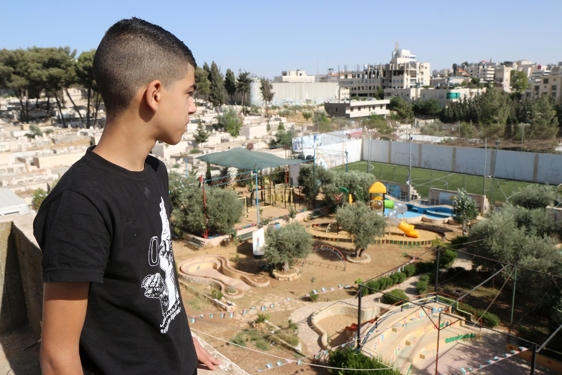 Leith Hammad, 14, looks at the recreational area and military base next to Lajee center. (Photo: DCIP/ Ahmad Al-Bazz)