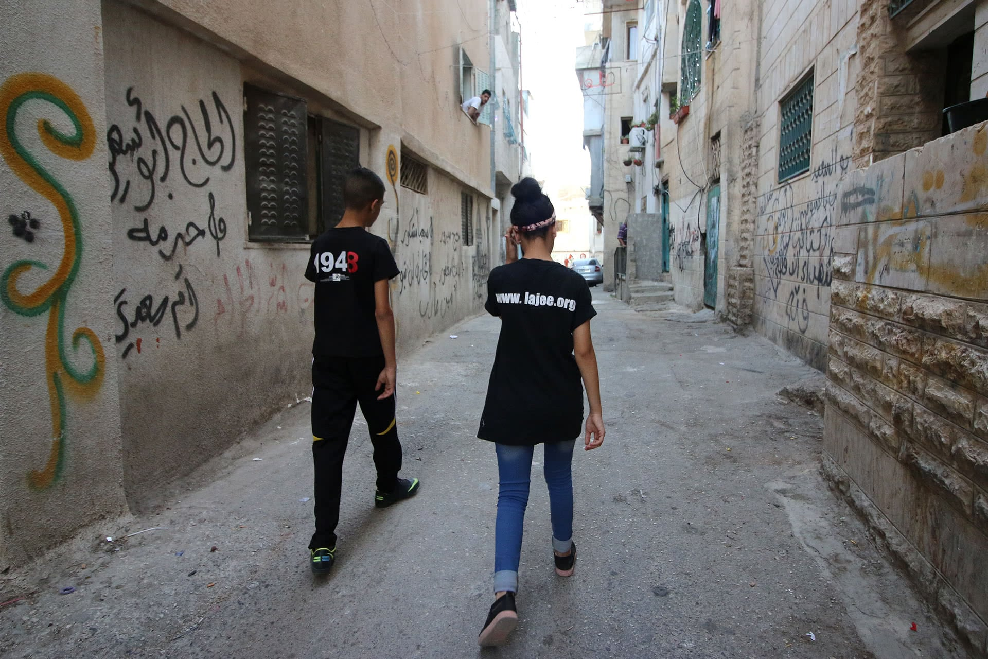 Leith and Shahd walk near Shahd's family home in the alleyways of Aida refugee camp. (Photo: DCIP / Ahmad Al-Bazz)
