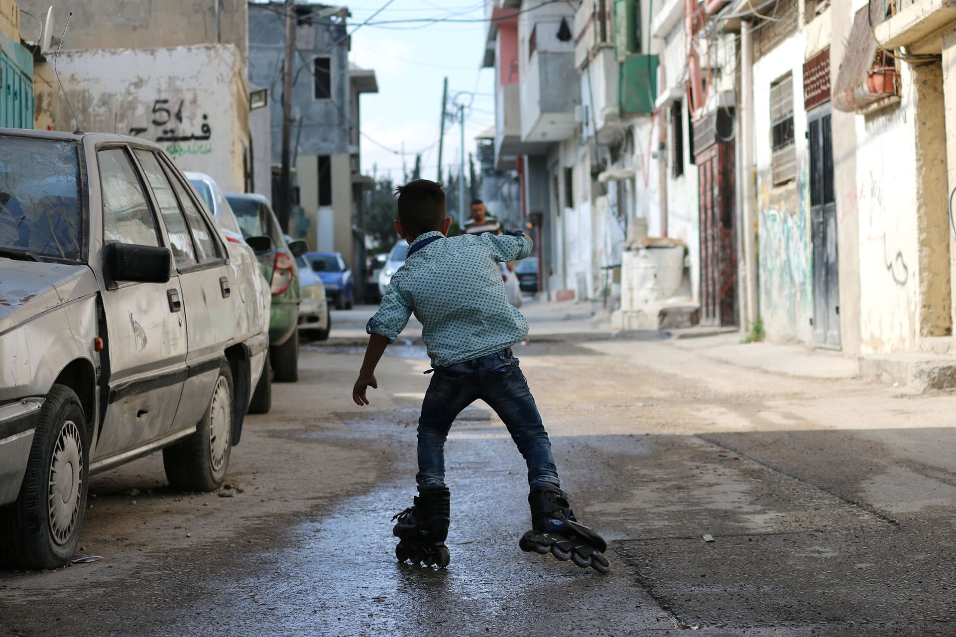 A child rollerblades down a small street in Arroub refugee camp. (Photo: DCIP / Ahmad Al-Bazz)