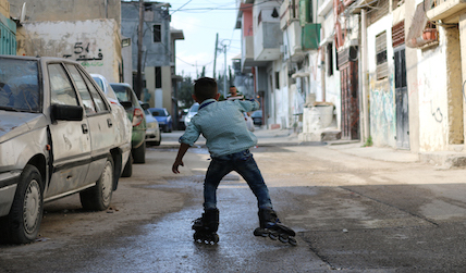 A child rollerblades down a narrow street in Arroub refugee camp.