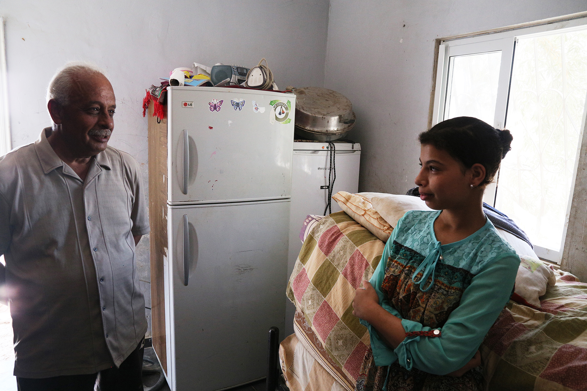 Bayan talks to her father in their tight kitchen, beside a bed stacked with mattresses. (Photo: DCIP / Ivan Karakashian)