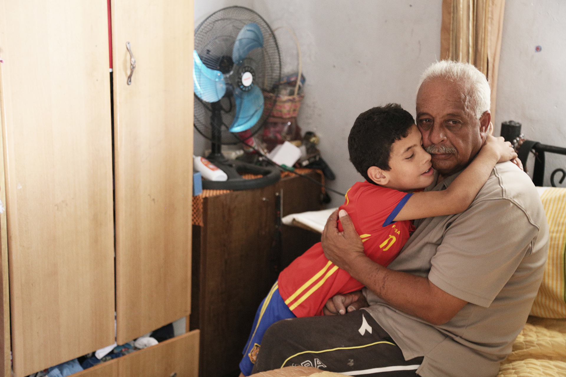 Ayham, the youngest child in the Fawaka family, hugs his father. (Photo: DCIP / Ivan Karakashian)