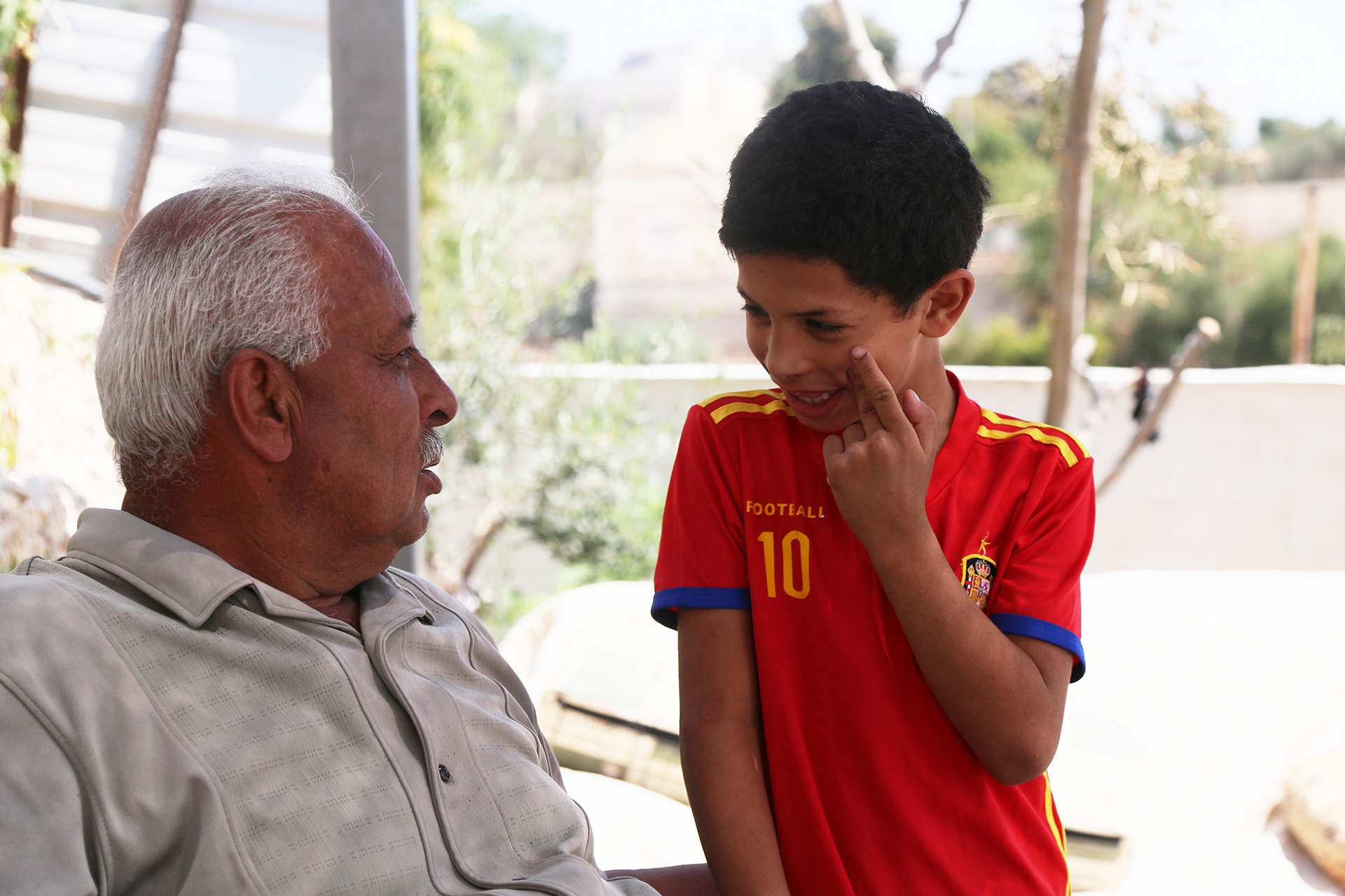 Ayham, the youngest child in the Fawaka family, plays with his father. (Photo: DCIP / Ivan Karakashian)