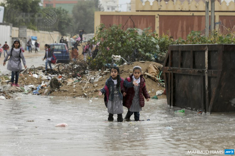 Palestinian school girls walk in a flooded street during heavy rain in Gaza City on November 21, 2017. (Photo: AFP / Mahmud Hams)