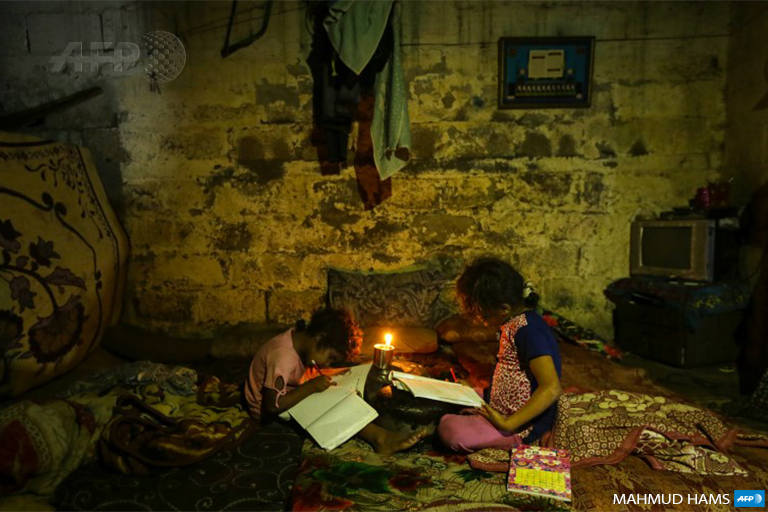 Palestinian children doing their homeworks during a power cut in an impoverished area in Gaza City, on September 11, 2017. (Photo: AFP / Mahmud Hams)