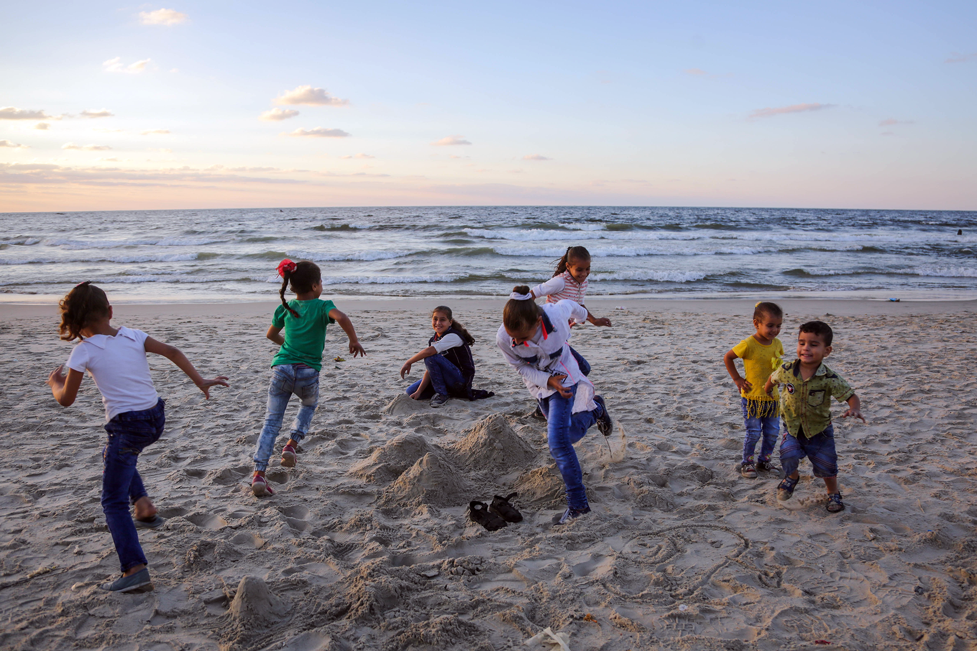 Relatives play on a beach nearby the site where six-year-old Mohammad was exposed to contaminated seawater and later died. (Photo: DCIP / Ezz Zanoun)