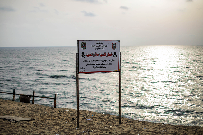 A municipal sign forbids fishing and swimming on one of the Gaza Strip's many beaches. (Photo: DCIP / Ezz Zanoun)