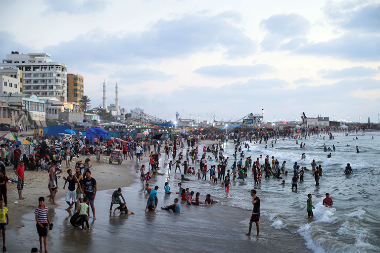 Palestinians seek reprieve from the heat on a beach near Gaza City's port, less than a kilometer south from the area where the al-Sayes children were exposed to contaminated seawater. (Photo: DCIP / Ezz Zanoun)
