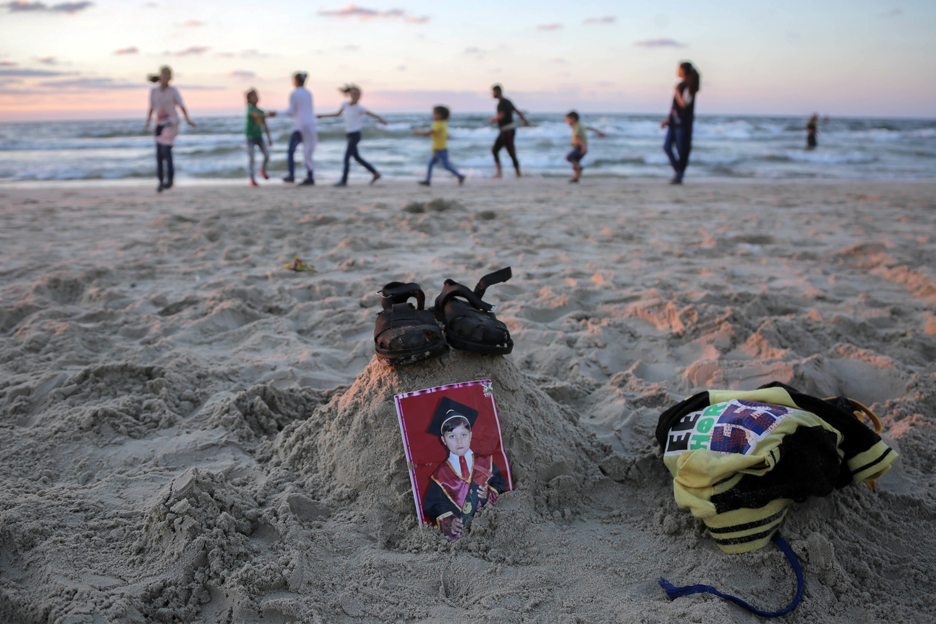 Mohammad's surviving siblings and cousins run on a beach on October 12 behind a makeshift memorial of his sandals and clothing. (Photo: DCIP / Ezz Zanoun)