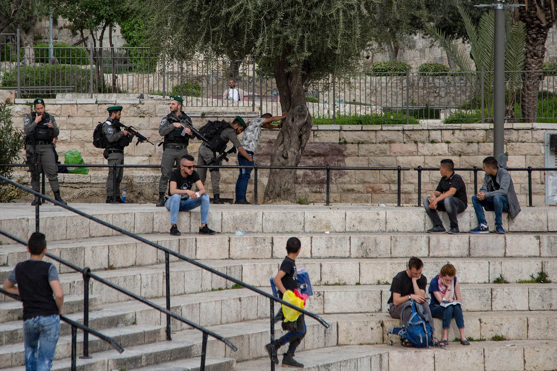 Israeli police forces body search a Palestinian youth near Damascus gate in the Old City of Jerusalem as a group of others watch. (Photo: Faiz Abu Rmeleh)