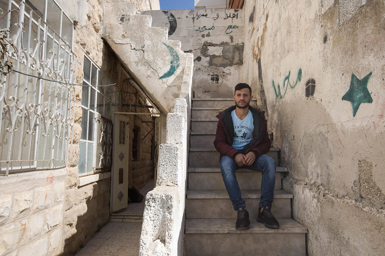Mohammad Abu Rmeileh sits on the steps during a visit to inspect damage to his former place of residence in Wadi Hilweh, Silwan. (Photo: Faiz Abu Rmeleh)