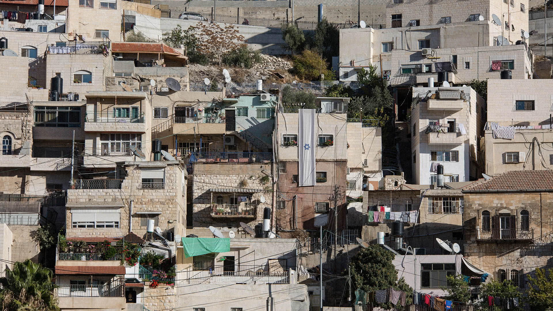 An Israeli flag hangs from a house inhabited by Israeli settlers in the Palestinian neighborhood of Silwan on May 4, 2017. (Photo: Faiz Abu Rmeleh)