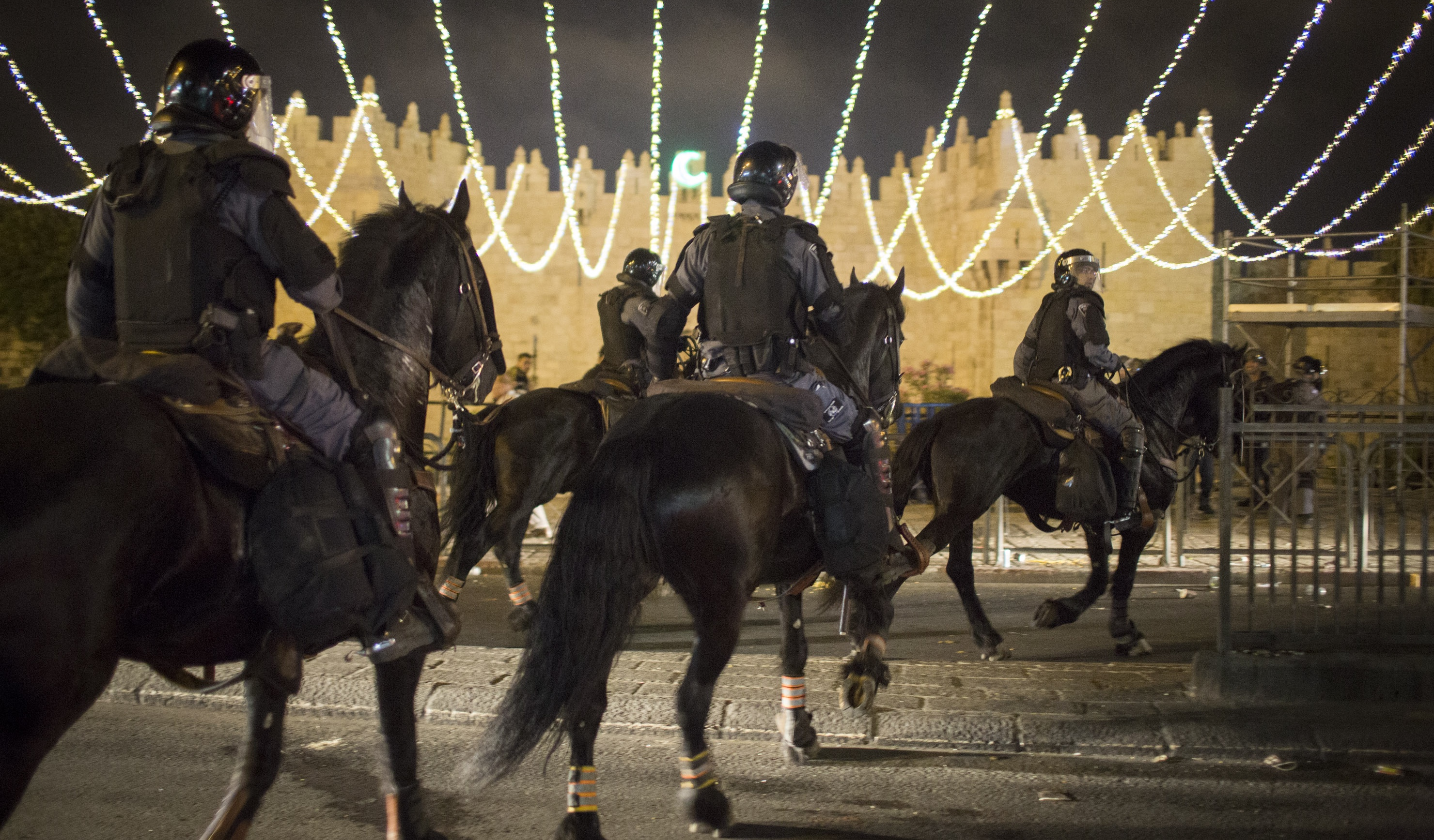 Mounted Israeli policemen disperse Palestinians at the end of the Ramadan fast, outside Jerusalem's old city, June 21, 2015. (Photo: ActiveStills / Oren Ziv)
