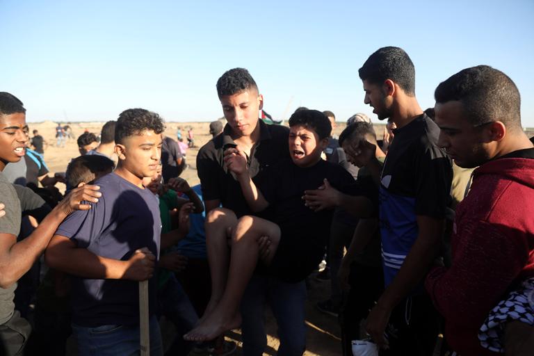 Palestinian protesters evacuate an injured boy suffocating from tear gas , east of Gaza City, Gaza Strip, November 2, 2018. (Photo: ActiveStills / Mohammed Zaanoun)