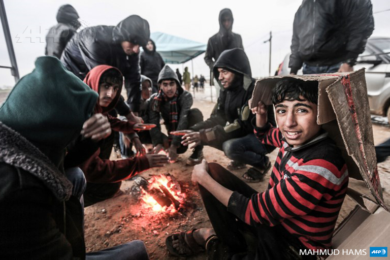 Palestinian youths and protesters sit together around a fire as they seek shelter from the rain, during a demonstration near the border with Israel east of Gaza city on December 28, 2018. (Photo: AFP / Mahmud Hams)
