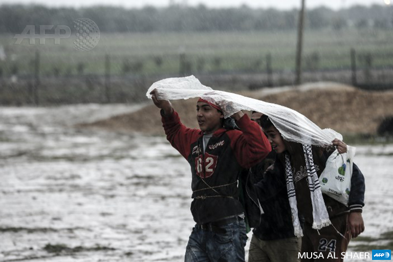 Palestinian protesters gather together under a plastic rain-cover during a demonstration near the border with Israel east of Gaza city on December 28, 2018. (Photo: AFP / Mahmud Hams)