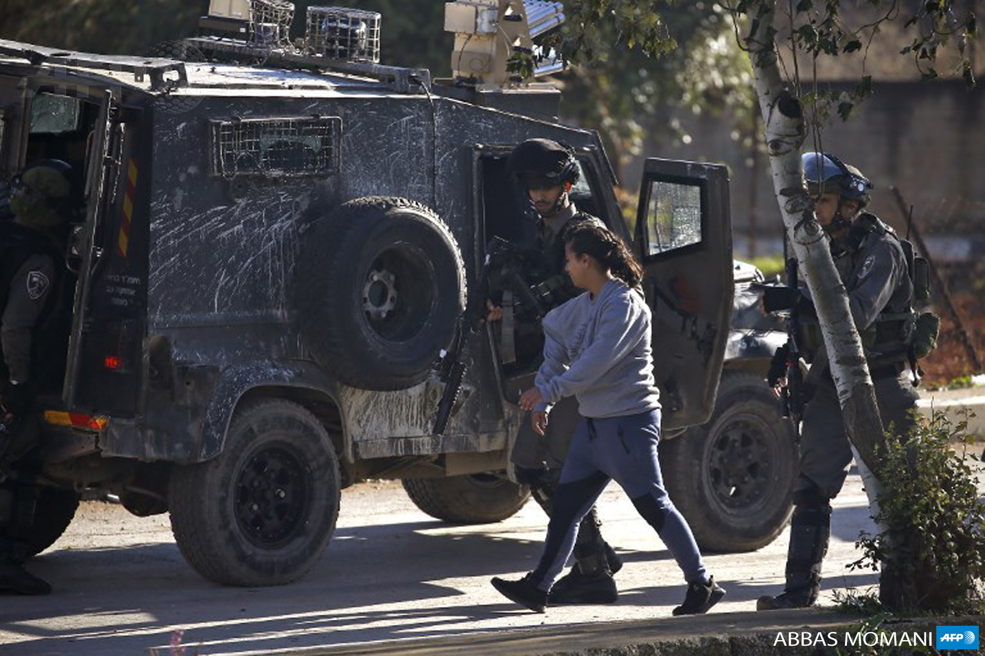 Israeli soldiers detain a Palestinian girl during clashes between Palestinian demonstrators and Israeli troops in Ramallah, near the Jewish settlement of Beit El, in the occupied West Bank on December 13, 2018. (Photo: AFP / Abbas Momani)