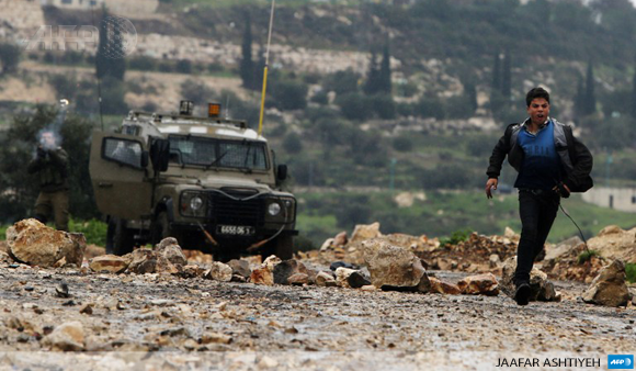 A Palestinian runs away from Israeli forces during clashes in the West Bank village of Kfar Qaddum on January 9, 2015.