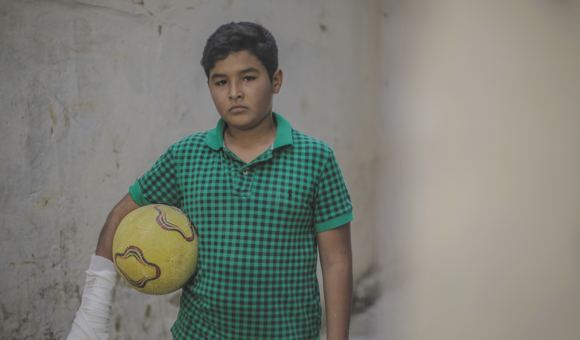 Samer poses for a photograph with his soccer ball in an alley outside his home on May 26, 2019. (Photo: DCIP / Mohammad Ibrahim)