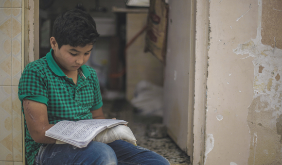 Samer looks at old homework in his own handwriting that he had completed before his injury, in his home in Jabalia refugee camp in the northern Gaza Strip, on May 26, 2019. (Photo: DCIP / Mohammad Ibrahim ).