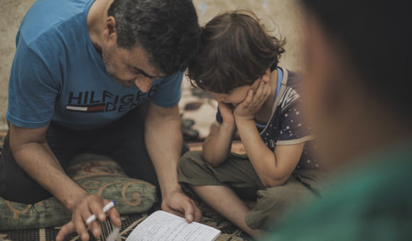 Samer watches his father, Abdel-Mohsen, while he helps his youngest child work on his homework. (Photo: DCIP / Mohammad Ibrahim)
