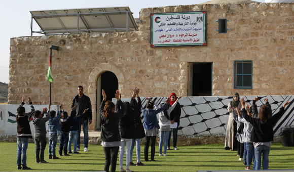 Children perform their morning exercises in the yard at the start of the school day. (Photo: DCIP / Majdi al-Sharif)